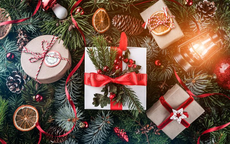 Christmas gift boxes with red decoration, pine cones, lamp on tree branches background with snowflakes. Xmas and Happy New Year. Theme, bokeh, sparking, glowing royalty free stock image