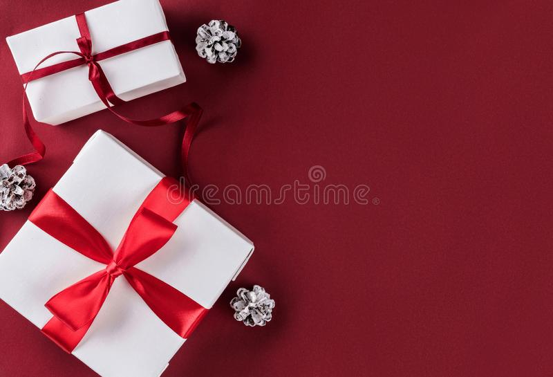 Christmas gift boxes with red ribbon, decoration, pine cones on white and red paper background. stock photography