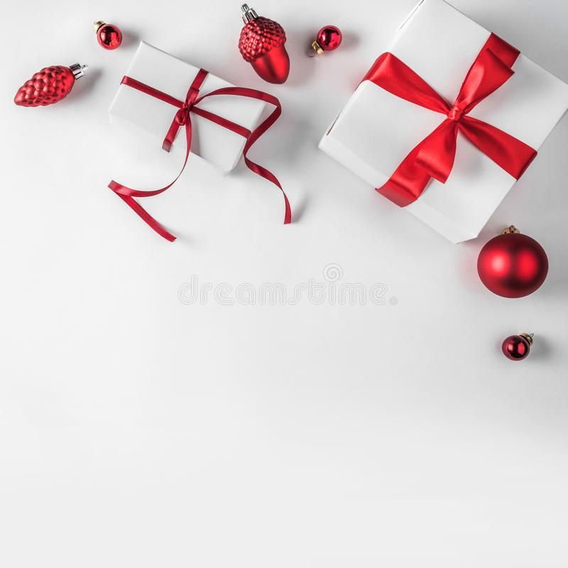 Christmas gift boxes with red ribbon and decoration on white background. Xmas and Happy New Year theme. Flat lay, top view stock image