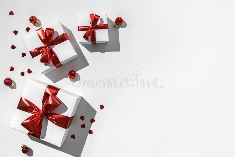 Christmas gift boxes with red ribbon and decoration on white background. Xmas and Happy New Year holiday, bokeh, light. Flat lay. Top view, harsh shadow stock photos