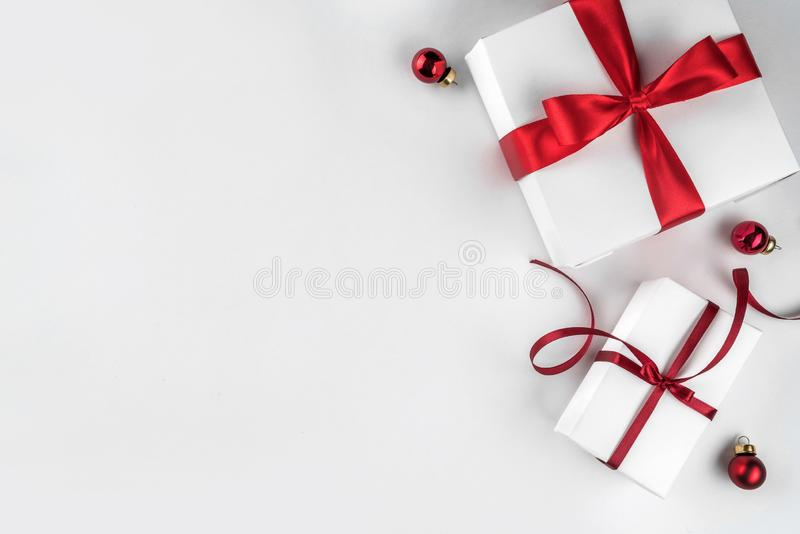 Christmas gift boxes with red ribbon and decoration on white background. Xmas and Happy New Year theme. Snow. Flat lay, top view, wide composition royalty free stock photography