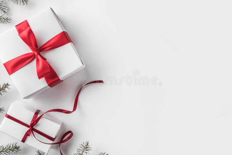 Christmas gift boxes with red ribbon on white background with Fir branches. Xmas and Happy New Year theme. Flat lay, top view, space for text royalty free stock image