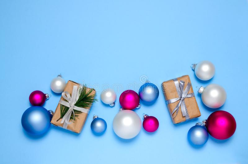 Christmas gift boxes with silver ribbon bow surrounded with Christmas balls. Christmas gifts on a blue background. Pastel colors. stock photo