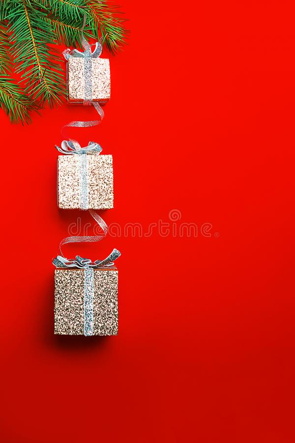 Christmas gift boxes on tree on red background. Christmas decoration with silver boxes as gift on branch fir tree on red background. Merry Christmas, New Year royalty free stock photos