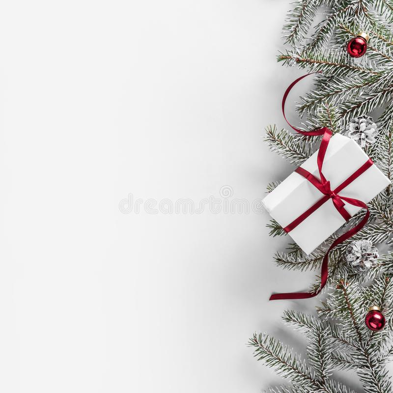 Christmas gift boxes on white background with Fir branches, pine cones, red ribbon. Xmas and Happy New Year theme. Flat lay, top view stock image