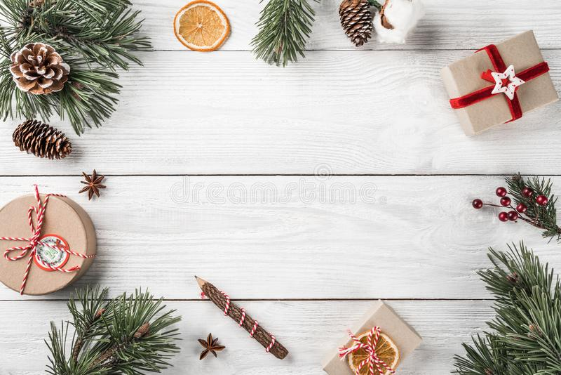 Christmas gift boxes on white wooden background with Fir branches, pine cones. Xmas and Happy New Year theme. Flat lay, top view, space for text stock photography