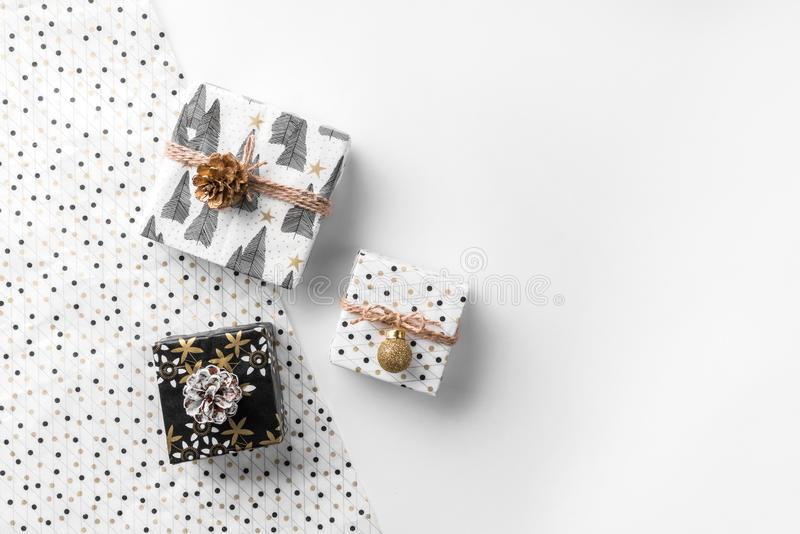 Christmas gift boxes on wrap background with gold decoration and pine cones. Xmas and Happy New Year theme. Flat lay, top view, wide composition stock image