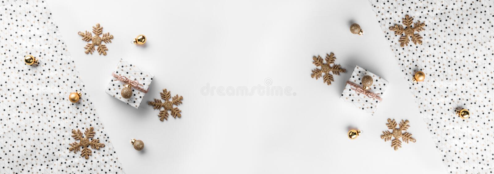Christmas gift boxes on wrap background with gold decoration and pine cones. Xmas and Happy New Year theme. Flat lay, top view, wide composition royalty free stock photo
