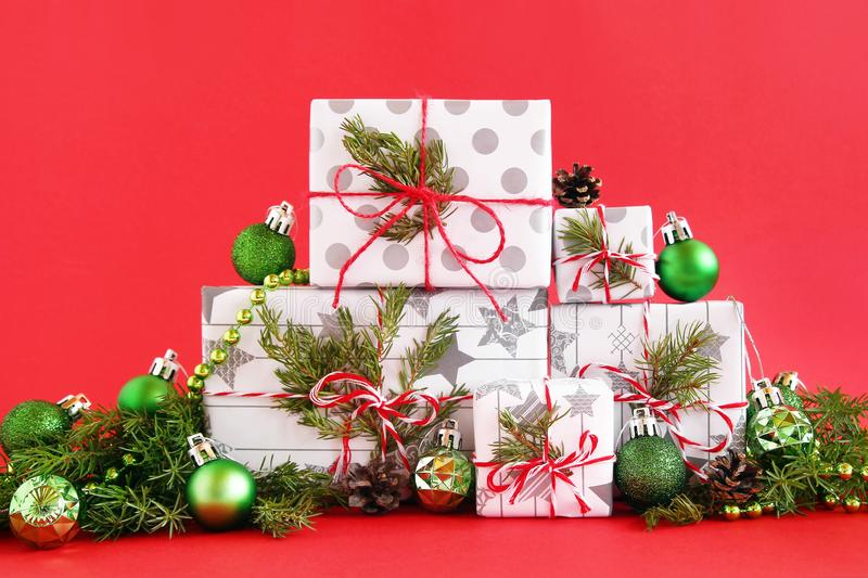 Christmas gift boxes on a red background, decorated of fir branches, pine cones and shiny green Christmas decorations. royalty free stock image