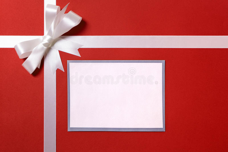 Christmas gift card or label and envelope, white ribbon bow, red. Wrapping paper background royalty free stock images