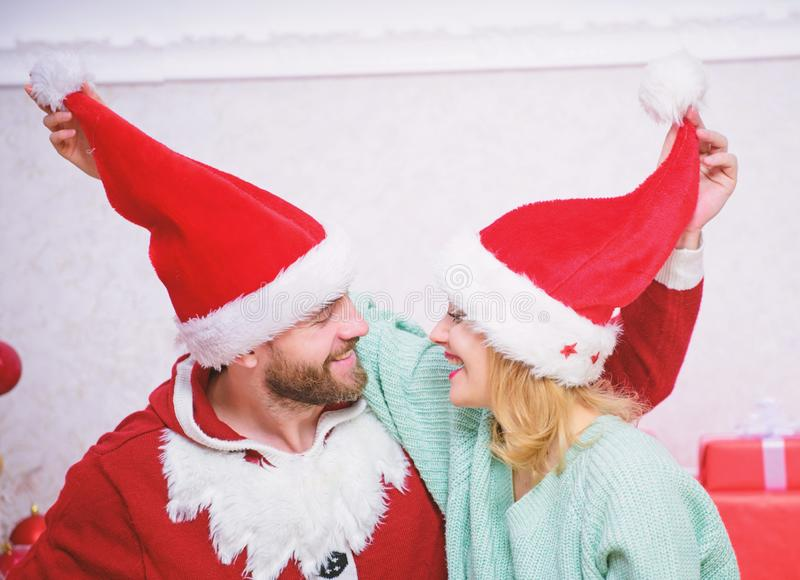 Christmas gift concept. Couple in love enjoy christmas celebration. Couple wear hats as santa claus christmas tree. Background. It is easy to spread happiness stock images