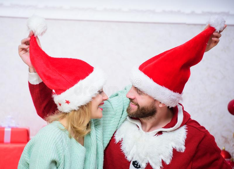 Christmas gift concept. Couple in love enjoy christmas celebration. Couple wear hats as santa claus christmas tree. Background. It is easy to spread happiness stock photo