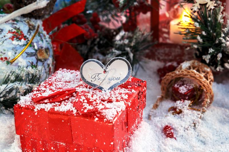 Christmas gift covered with snow in the light of a red lantern on the background of New Year`s scenery. Christmas and New Year stock photo