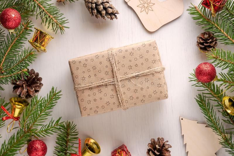 Christmas gift in craft paper with twine on white background. Christmas gift wrapped in craft paper with twine on white background, surrounded by pine cones stock photos