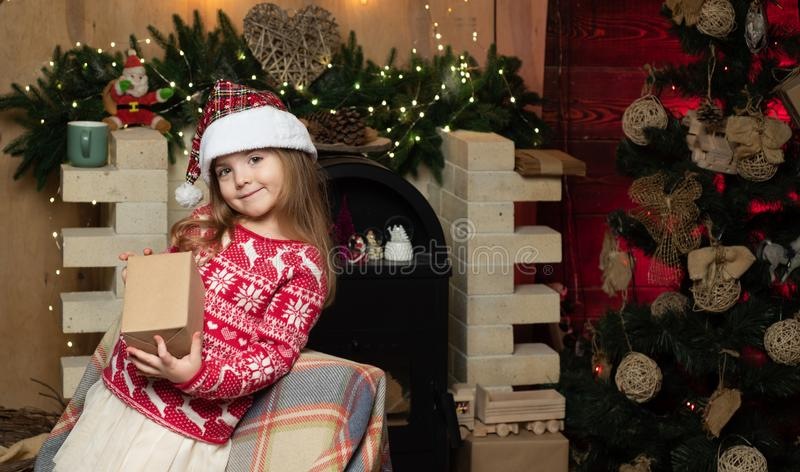 Christmas gift. Cute little child girl play near christmas tree. Kid enjoy winter holiday at home. Home filled with joy stock photos