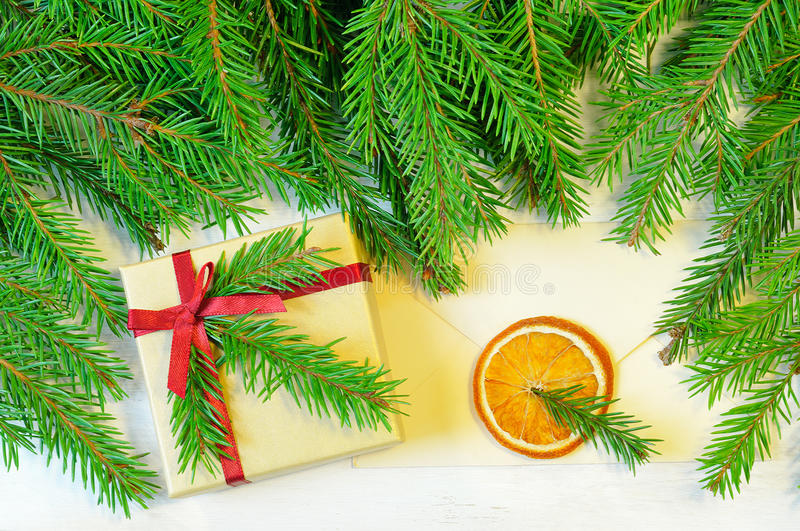 Christmas gift decorated with Christmas tree twig and envelope royalty free stock photography