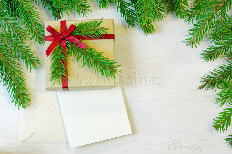 Christmas gift decorated with Christmas tree twig, envelope and stock photo