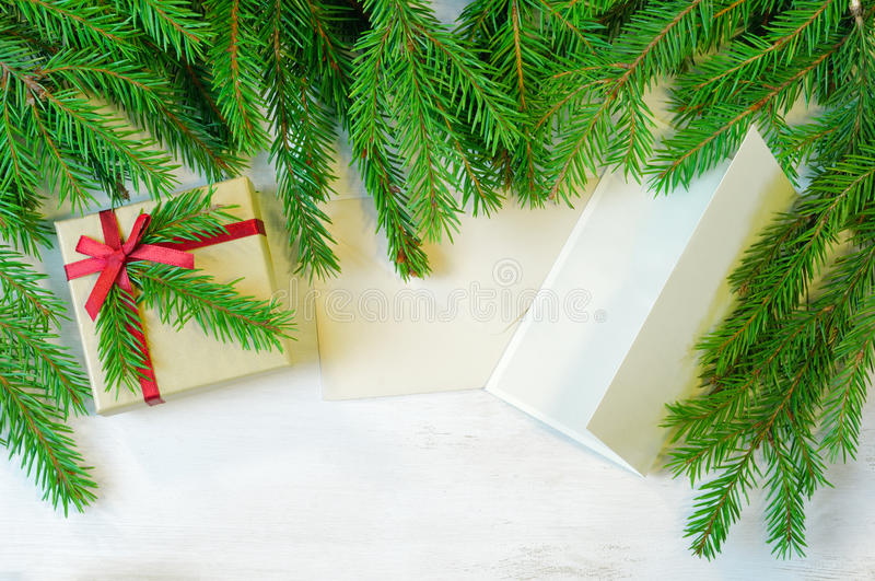 Christmas gift decorated with Christmas tree twig, envelope and royalty free stock photography