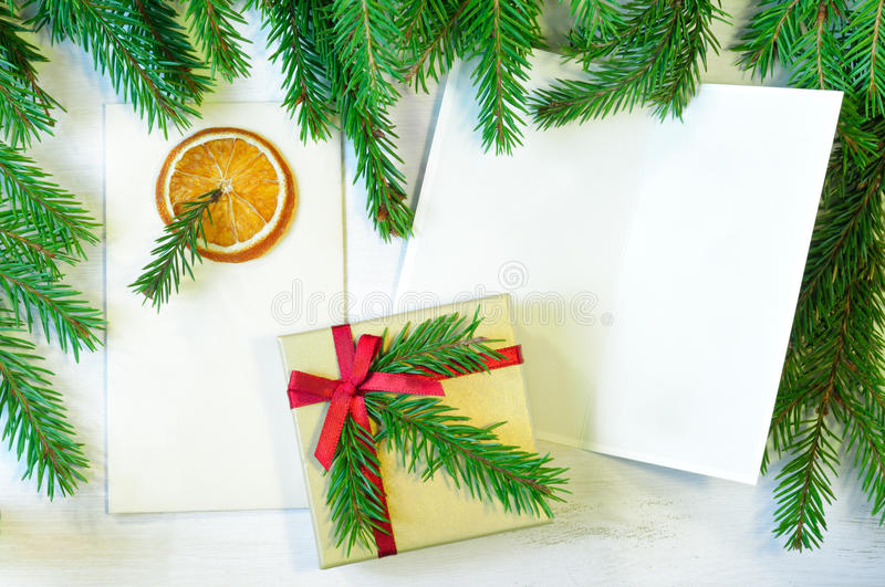 Christmas gift decorated with Christmas tree twig, envelope and stock images