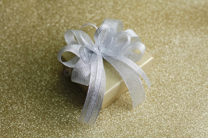 Christmas gift. On Decorative background in gold with sparkling stars royalty free stock photography