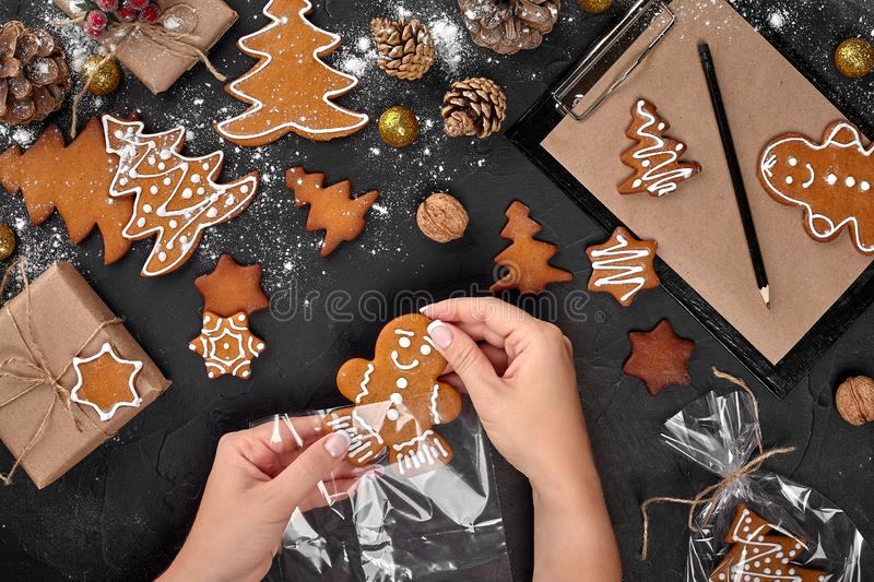 Christmas gift gingerbread on dark background. Biscuits in festive packaging. Woman is packaging Christmas gingerbread. Christmas gift gingerbread on dark stock photos