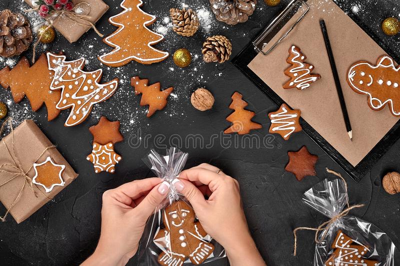 Christmas gift gingerbread on dark background. Biscuits in festive packaging. Woman is packaging Christmas gingerbread. Christmas gift gingerbread on dark stock photo