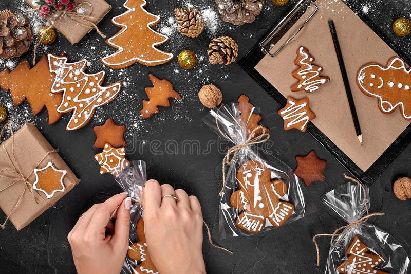 Christmas gift gingerbread on dark background. Biscuits in festive packaging. Woman is packaging Christmas gingerbread. Christmas gift gingerbread on dark royalty free stock photography