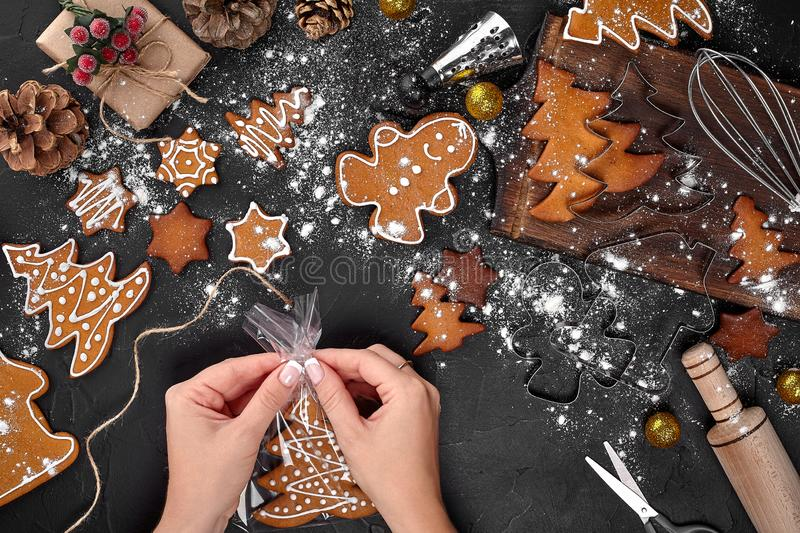 Christmas gift gingerbread on dark background. Biscuits in festive packaging. Woman is packaging Christmas gingerbread. Christmas gift gingerbread on dark stock images