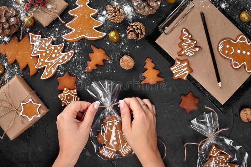Christmas gift gingerbread on dark background. Biscuits in festive packaging. Woman is packaging Christmas gingerbread. Christmas gift gingerbread on dark royalty free stock photo