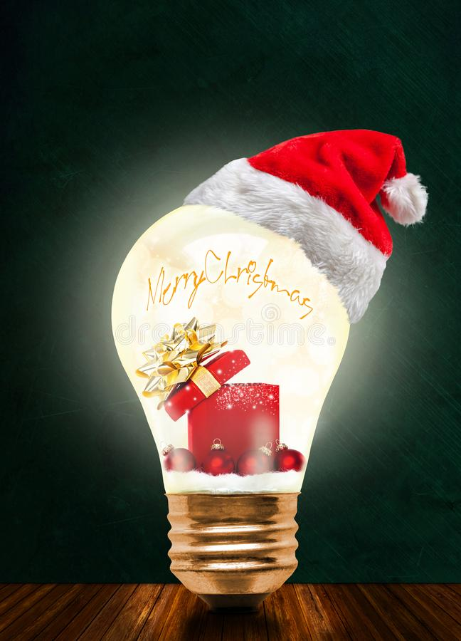 Christmas Gift in Glowing Light Bulb With Santa Hat And Copy Spa royalty free stock photos
