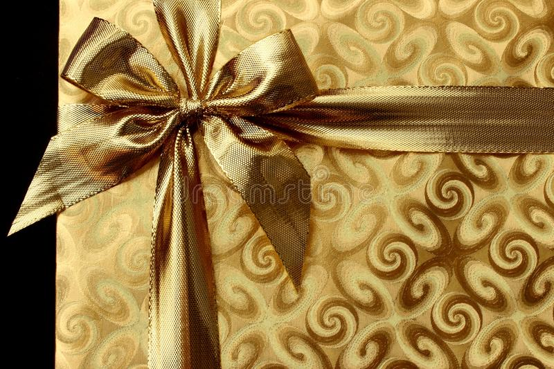Christmas gift in gold paper with bow. background. Image of Christmas gift in gold paper with bow. background royalty free stock image