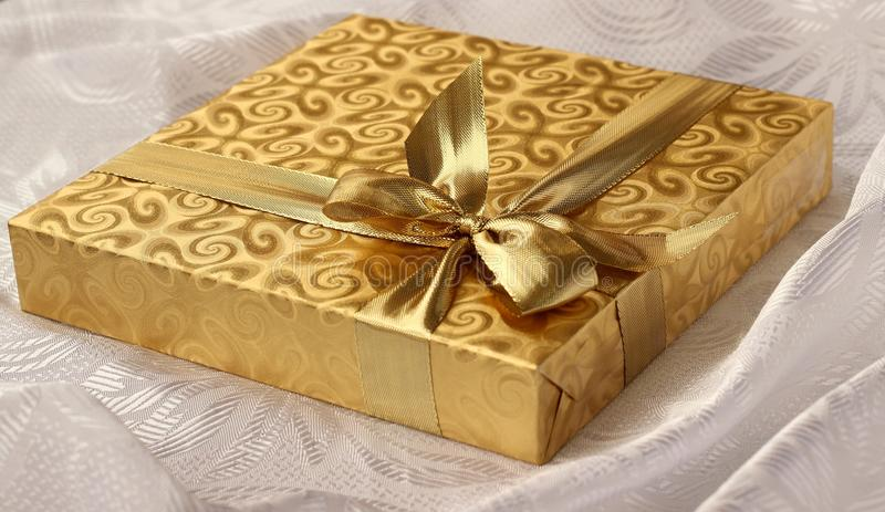 Christmas gift in gold paper with bow on white background stock photography