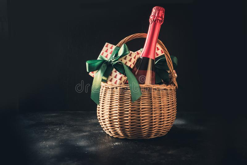 Christmas gift hamper with champagne and gift on black. Space for your greetings. greeting card. Christmas gift hamper with champagne and gift with green bow on stock photos
