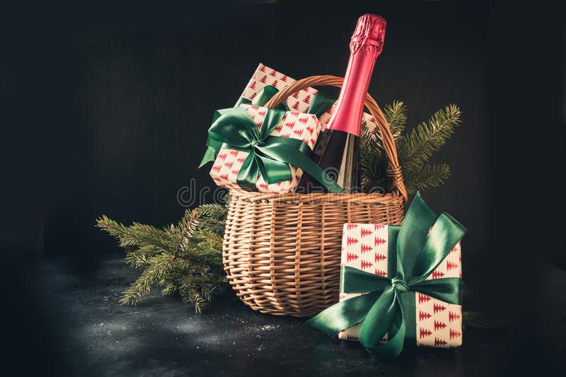 Christmas gift hamper with champagne and gift on black. Space for your greetings. greeting card. Christmas gift hamper with champagne and gift on black. Space stock photos