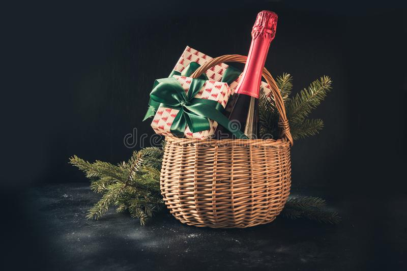 Christmas gift hamper with champagne and gift on black. Space for your greetings. greeting card. Christmas gift hamper with champagne and gift with green bow on stock photo