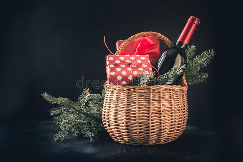 Christmas gift hamper with red wine and gift on black. Space for your greetings. Xmas card. Christmas gift hamper with red wine and gift on black. Space for your stock images