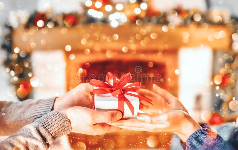 Christmas Gift in hands. Happy Man giving Christmas and New Year Gift box to woman at Home. Family Xmas celebration. Person Holding, Receiving a Gift box stock photography