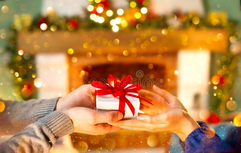 Christmas Gift in hands. Happy Man giving Christmas and New Year Gift box to woman at Home. Family Xmas celebration. Person Holding, Receiving a Gift box royalty free stock images