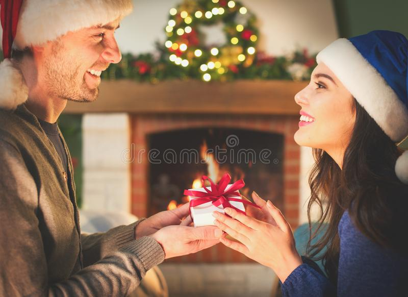 Christmas Gift in hands. Happy Man giving Christmas and New Year Gift box to woman at Home. Family Xmas celebration royalty free stock image