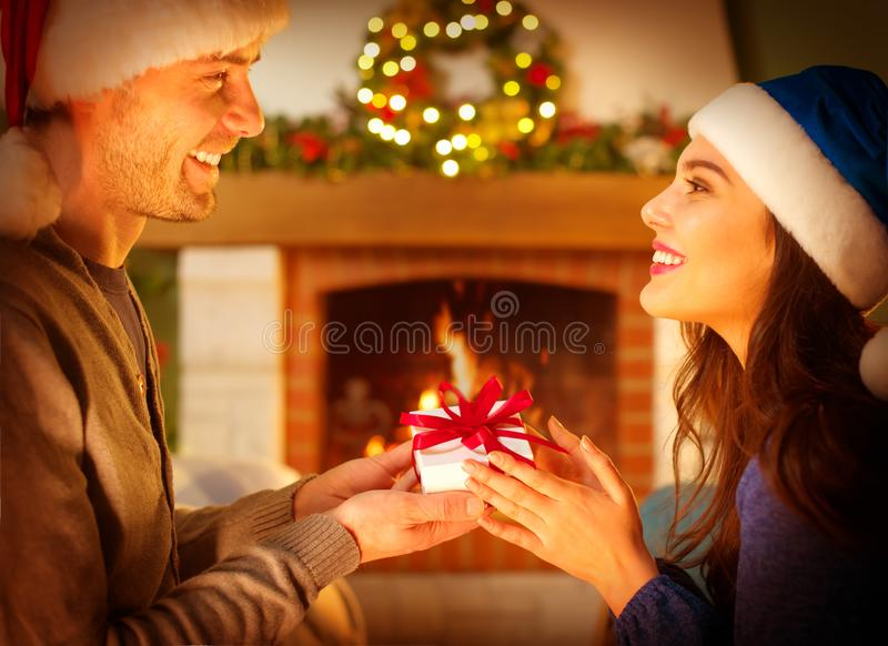 Christmas Gift in hands. Happy Man giving Christmas and New Year Gift box to woman at Home. Family Xmas celebration stock photography