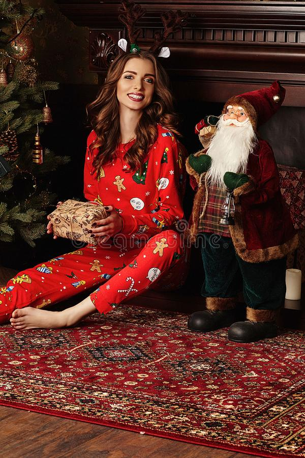 Christmas Gift. Happy Surprised Woman with brunette curly hair , dressed in a Christmas suit, opening Gift box at home. Christmas stock image
