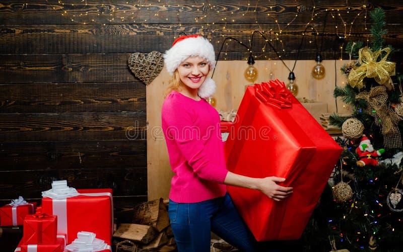 Christmas gift. Portrait of beautiful girl wearing Santa clothes. Blonde Santa woman holding gift box at vintage wall royalty free stock image