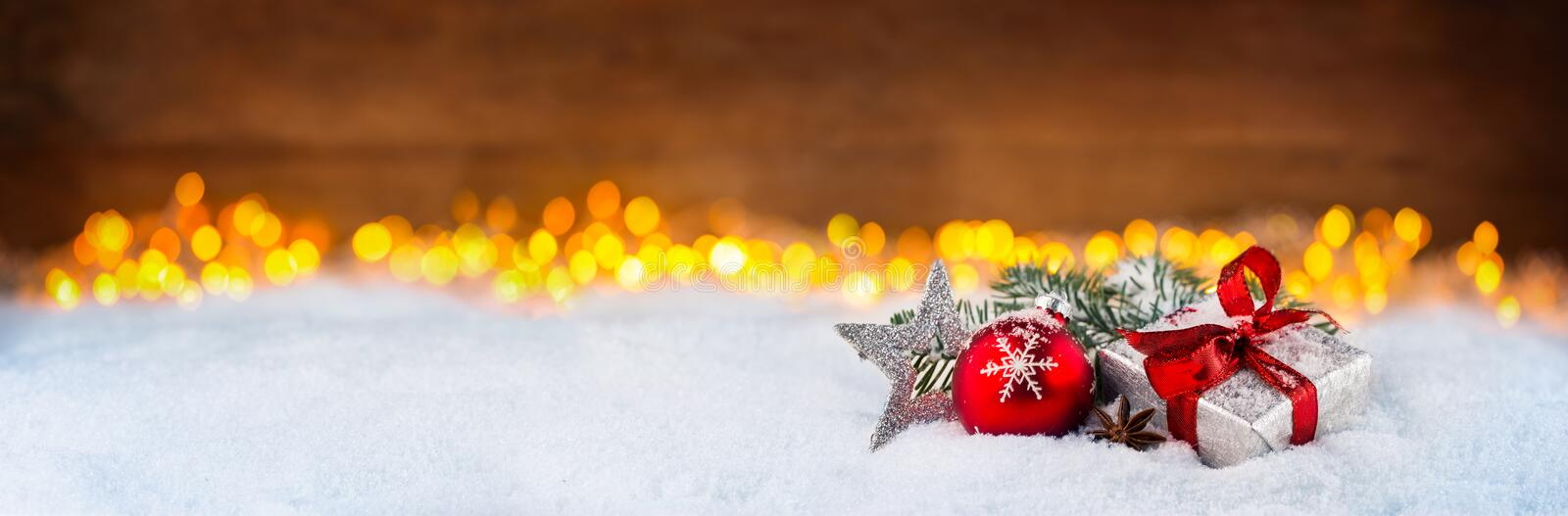Christmas gift present box ribbon red star silver decoration bauble on snow in front of bright lights golden warm bokeh wide royalty free stock photo