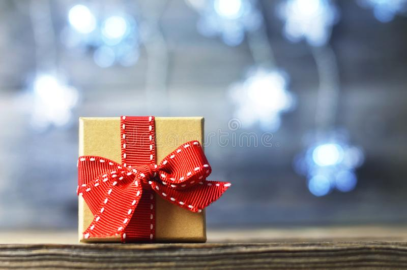 Christmas gift with red ribbon. On wooden background royalty free stock image
