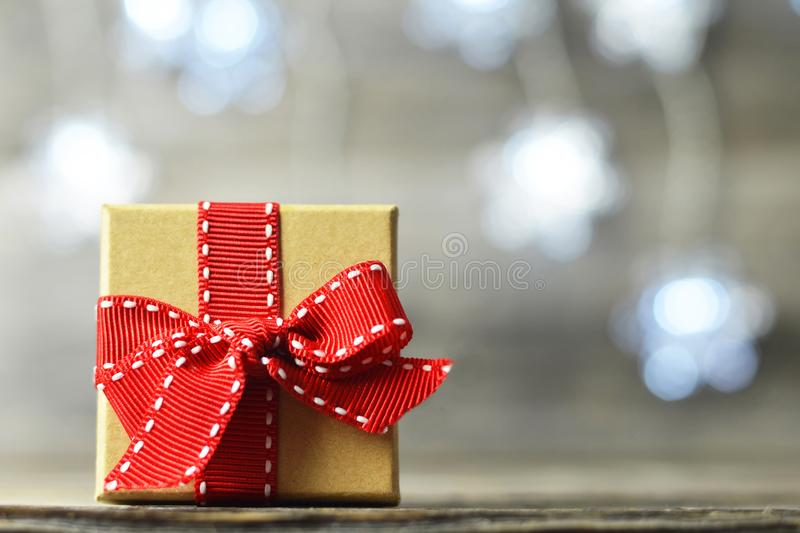 Christmas gift with red ribbon. On wooden background stock image