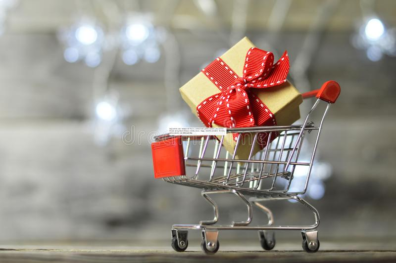 Christmas gift shopping. Shopping cart and gift box. On wooden background royalty free stock photos