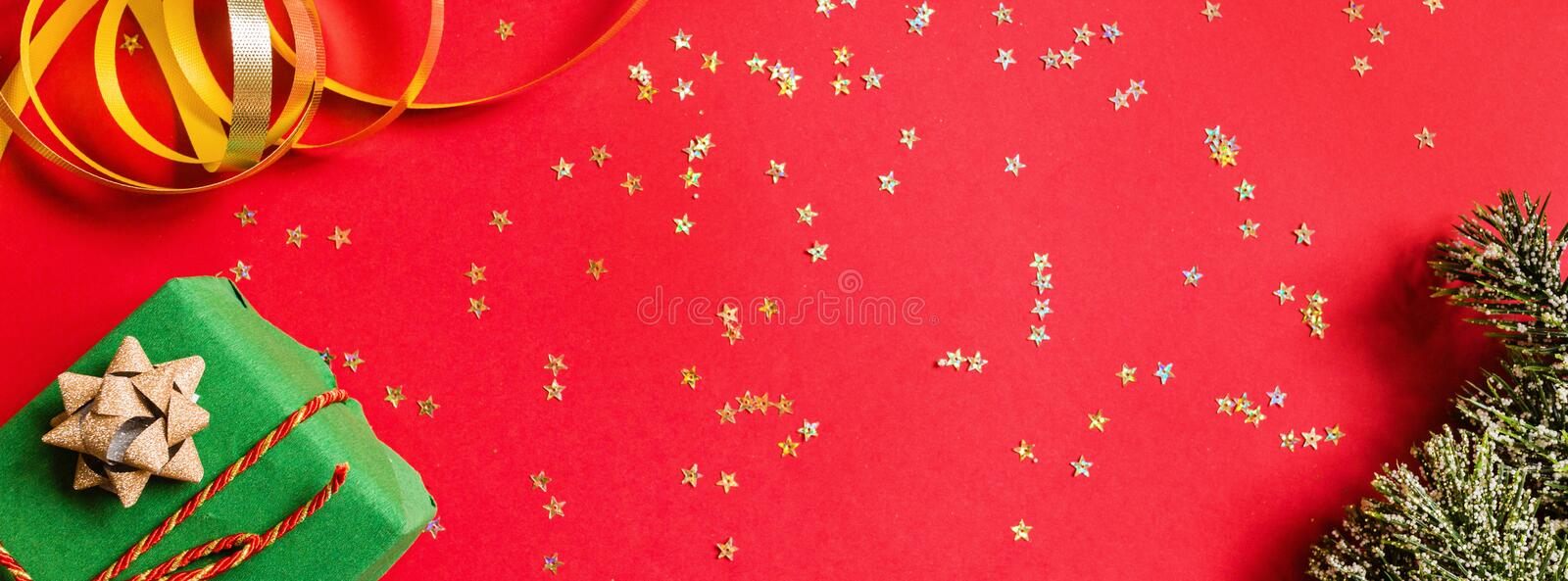 Christmas gift, tree branches on red background with golden confetti. Horizontal banner for web design. new year concept. Greeting stock photo