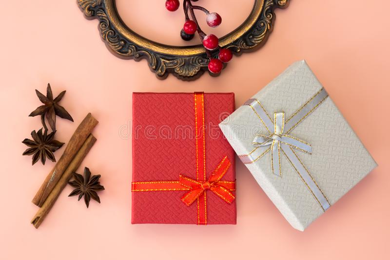 Christmas gift. Two gift boxes, cinnamon, anise, holly and retro frame on pink background. Top view. Xmas and New year`s day concept royalty free stock photography