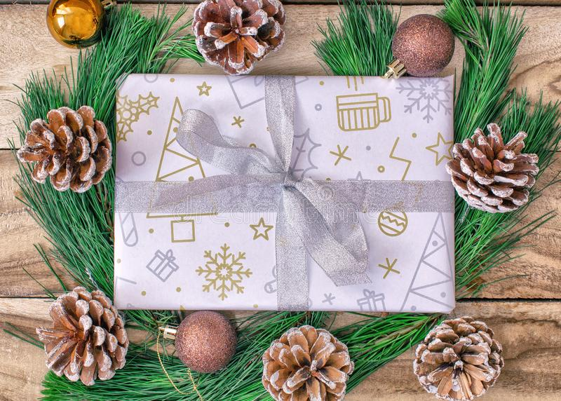 Christmas gift wrap, gift paper, gift boxes, fir trees, with cones and decorations on a wooden background. stock image