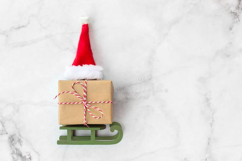 Christmas gift wrapped in brown craft paper and red hat on wooden sleigh Christmas toys on gray marble background. New Year, royalty free stock image
